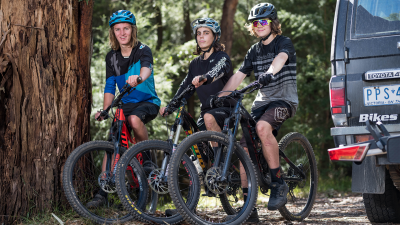 Three mountain bikers sitting on their bikes in the forest after a ride