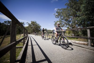 Three bike riders on Lilydale to Warburton rail trail bridge on sunny clear day with blue skies