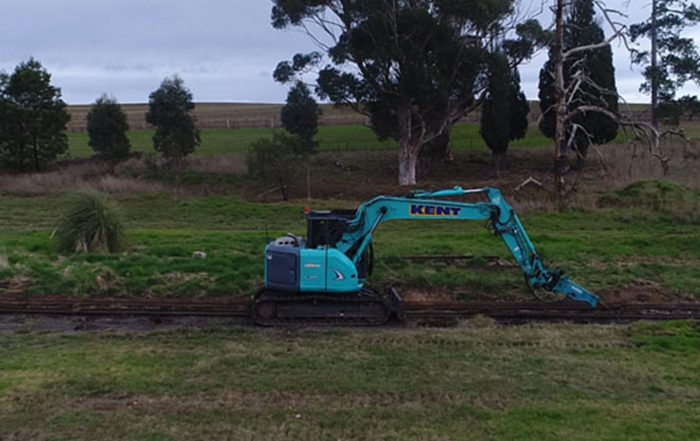 Blue excavator removing old rail lines in green field on overcast day at Coldstream