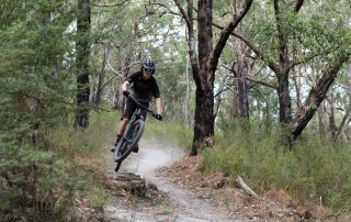 Mountain biker going over small jump at Hey Hey My My trail in Wesburn